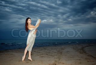 Sexy lady at the beach during the bad weather