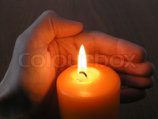 On a photo a burning candle on a black background and a hand protecting fire. The photo is made in Ukraine.