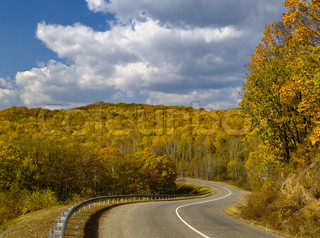 A landscape mountain road to an autumn wood Russia