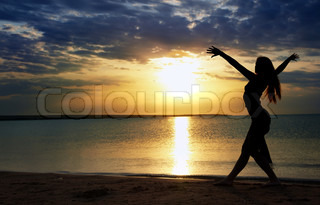Elegant lady dancing sportive aerobics at the beach during sunset