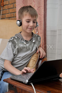Cute Boy Working On Laptop Computer at home