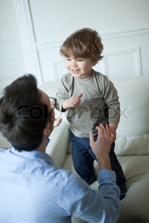 ©Sandro Di Carlo Darsa/AltoPress/Maxppp ; Toddler boy standing on couch, smiling at father