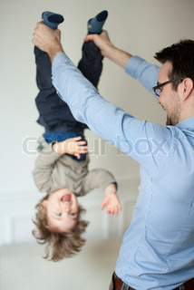 ©Sandro Di Carlo Darsa/AltoPress/Maxppp ; Father holding young son upside down by his ankles
