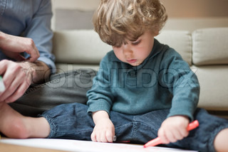 ©Sandro Di Carlo Darsa/AltoPress/Maxppp ; Toddler boy sitting on floor with father, drawing on paper
