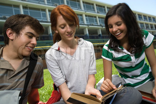 ©Frédéric Cirou/AltoPress/Maxppp ; Hight school student showing friends passage in book, sitting together on school lawn