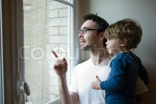 ©Sandro Di Carlo Darsa/AltoPress/Maxppp ; Father and toddler son looking out window together