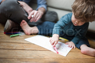 ©Sandro Di Carlo Darsa/AltoPress/Maxppp ; Toddler boy sitting on floor with parent, drawing on paper