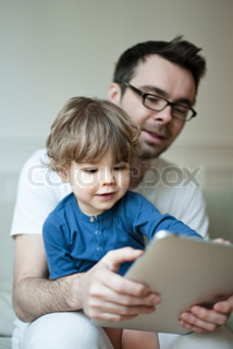 ©Sandro Di Carlo Darsa/AltoPress/Maxppp ; Father and young son looking at digital tablet together