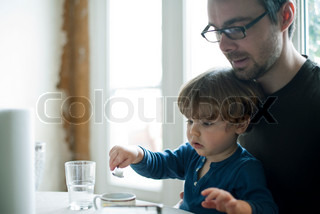 ©Sandro Di Carlo Darsa/AltoPress/Maxppp ; Toddler boy learning to use spoon, father watching affectionately