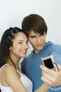 ©Laurence Mouton/AltoPress/Maxppp ; Young couple taking self portrait with digital camera, woman smiling at camera
