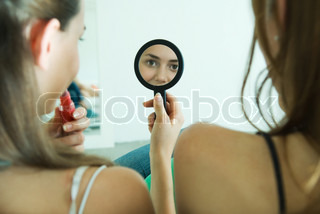 ©Odilon Dimier/AltoPress/Maxppp ; Teenage girl sitting next to friend, applying lipstick, looking at self in hand mirror, rear view