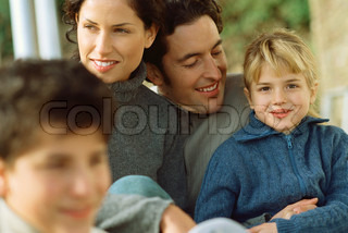 ©Eric Audras/AltoPress/Maxppp ; Little girl sitting with parents and brother, smiling at camera