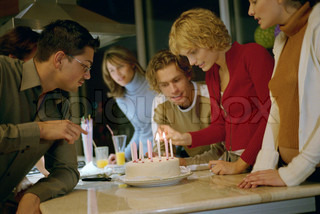 ©Eric Audras/AltoPress/Maxppp ; Woman lighting candles on birthday cake, others standing by watching
