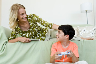 ©Odilon Dimier/AltoPress/Maxppp ; Young boy sitting on floor playing video game looking up at mother relaxing on sofa