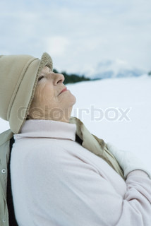 ©Laurence Mouton/AltoPress/Maxppp ; Senior woman standing in snowy landscape, looking up, waist up