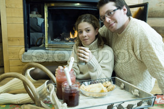 ©Laurence Mouton/AltoPress/Maxppp ; Young man and teen girl drinking hot drinks by fire place