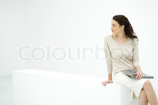 ©Eric Audras/AltoPress/Maxppp ; Young female professional sitting on ledge, holding binder, looking over shoulder