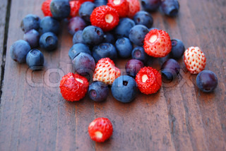 Scattering of blue and red forest berries on the wooden table