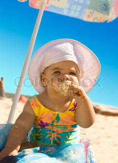 The little girl on the beach under an umbrella with ice cream