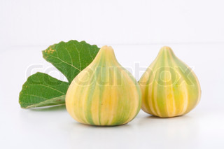 Ripe fruits of a fig on a white surface.