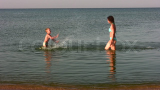 mother with boy splashing water
