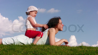 little girl on mother on meadow