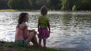 mother with girl on pond