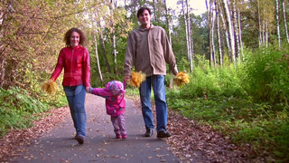 family with little girl walking in autumn park