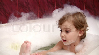 little girl in bath cleaning leg