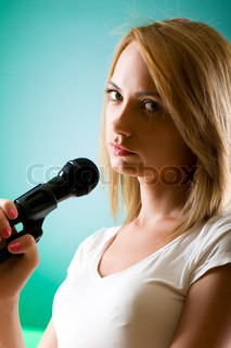 Girl singing with microphone against gradient background