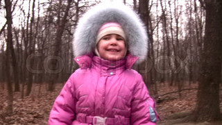 walking little girl in winter park to camera