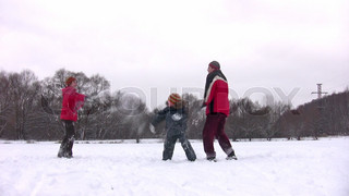 family with boy playing snowball