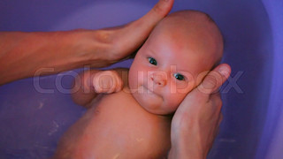 baby  in water on parents hands