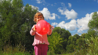little girl throwing up red balloon in park