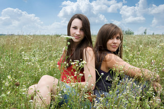 Two young attractive girls sitting in the grass in a meadow