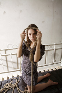 young woman with rope thinking about suicide