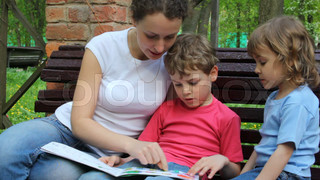 Mother reading book with kids