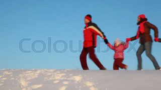 family walk on snow hill