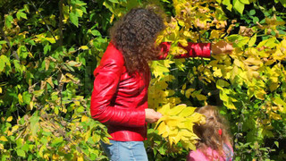 young woman with little girl gathering autumn leaves