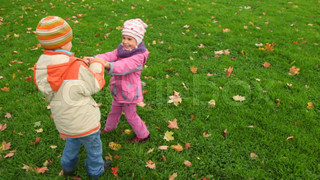 boy and little girl spinning on green grass with autumn leaves, join hands