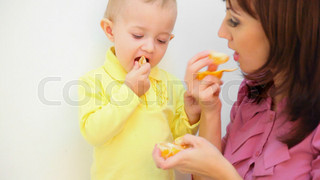 young mother and her little son eating orange against white background