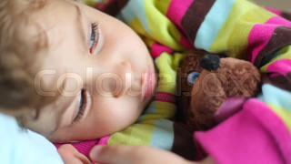 cute sleepy little girl with toy bear lying in bed and blinking