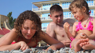 family fingering stones in pebble beach, hotel in background