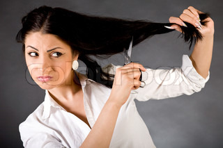 The young beautiful girl cuts off the dark hair scissors