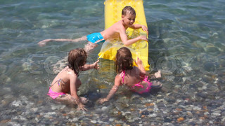 happy smiling kids playing with inflatable mattress in water of sea