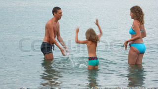 family of three persons standing in sea and plaiying with water, join hands