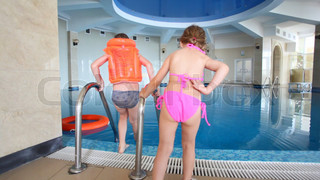 boy and little girl get ready to swimming in indoor pool