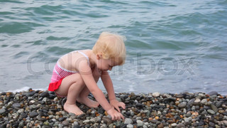 little girl sitting on pebble beach and playing with stones, sea in background