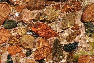 colorful stones under clean water with reflecting light