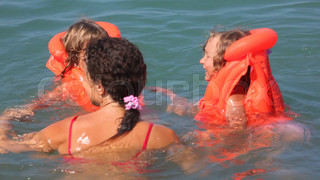 young woman with two little girls and boy on inflatable mattress has fun in sea